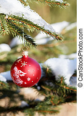 christmas balls on outdoor snowy tree