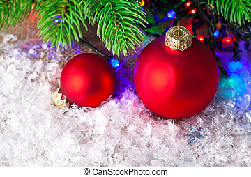 Christmas balls on white snow with branch fir tree
