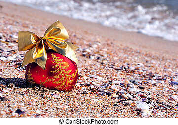 christmas bauble with golden bow on sand on beach