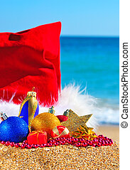 Christmas baubles and gift boxes in the christmas hat against the blue ocean