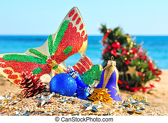 Christmas baubles, face mask, christmas tree in the beach
