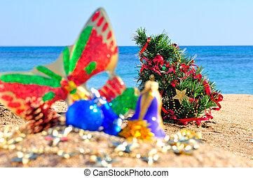 christmas baubles, face mask, christmas tree on sand