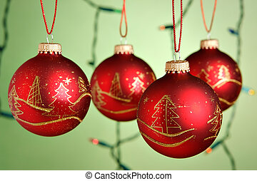 Christmas baubles hanging over green background