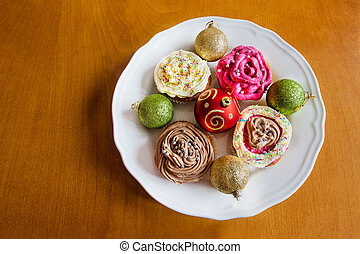 Christmas baubles with homemade cup cakes on wooden background
