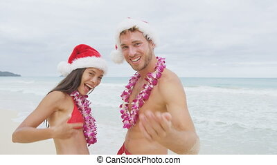 Christmas beach Hawaii couple saying welcome and come here showing hand gesture waving hand gesturing. Portrait of Asian woman and Caucasian man on beach wearing flower leis. RED EPIC SLOW MOTION.