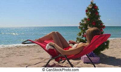 Christmas beach holidays background, bikini girl relaxing...