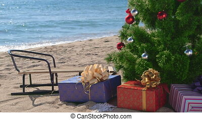Christmas beach holidays - decorated tree with gift boxes and sledge