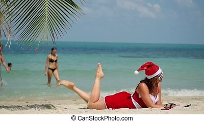 Christmas beach vacation travel woman wearing Santa hat and dress enjoying winter holidays on tropical beach of Koh Samui in slow motion. 1920x1080
