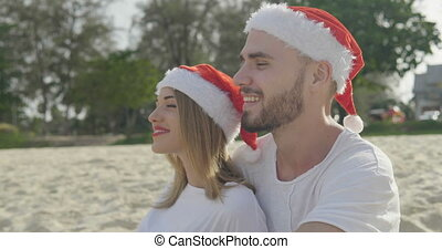 Christmas beautiful beach couple wearing santa hat in summer...