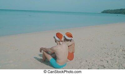 Christmas beautiful beach couple wearing santa hat in summer...