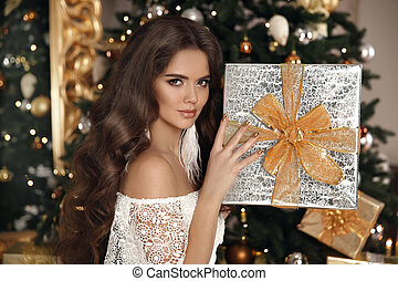 Christmas. Beautiful smiling woman with gift box. fashion interior photo of gorgeous brunette. Makeup. Healthy long hair style. Elegant lady in white dress over golden xmas tree lights background.