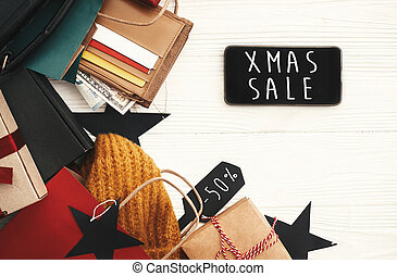 Christmas big sale text on phone screen. Special discount christmas offer. Phone with advertising message at money, wallet, bags, clothes, gift boxes, price tags. Shopping time