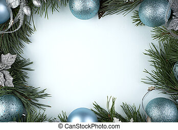 Christmas blue decorations and pine branches on a blue background.