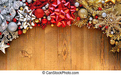 Christmas bows, ornaments, and decorations on wooden background