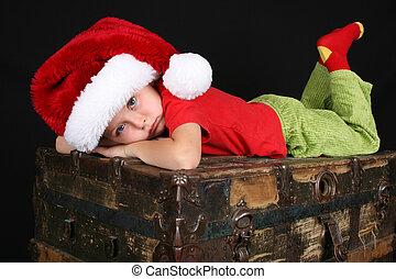 Christmas Boy - Sad boy wearing a christmas hat, ontop of an...