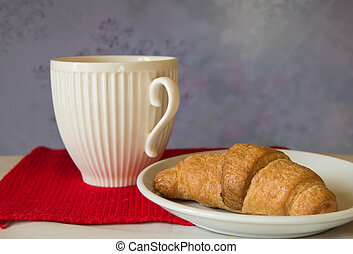 Christmas Breakfast - White Cup and croissant on a background of red knitted scarf
