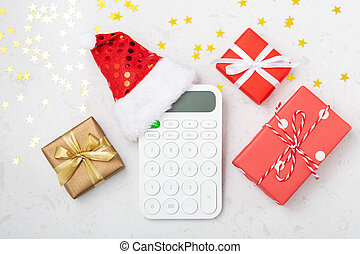 Christmas budget concept with calculator and gift boxes on marble background with glitter star, top view