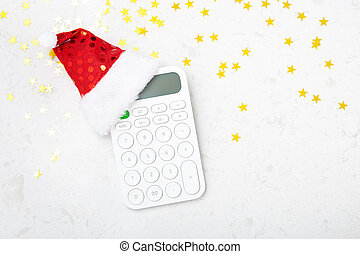 Christmas budget concept with christmas hat on calculator on marble background, flat lay