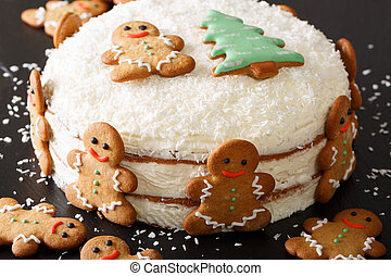 Christmas cake is decorated with gingerbread and coconut close-up. Horizontal