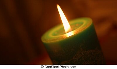 Christmas candle fire closeup with blurred background in Dutch angle