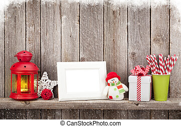 Christmas candle lantern, photo frame and decor in front of...