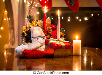 candles, gift box and woolen sock placed on table against firepl
