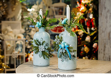 Christmas candlestick in shape of blue bottle decorated with fir tree and beads