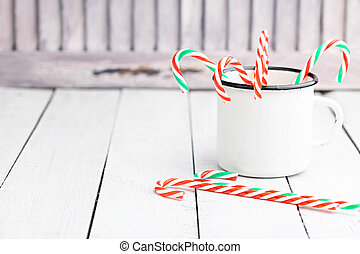 Christmas candy cane sticks in white tin cup. Light coloured photo. Space for text.