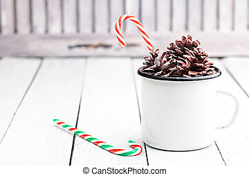 Christmas candy cane sticks in white tin cup with fir cones. Light coloured photo. Space for text.
