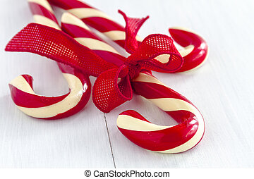 3 large red and white striped candy canes tied with red burlap ribbon sitting on white wooden table