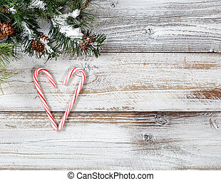 Christmas candy canes in heart shape with snowy rough fir...