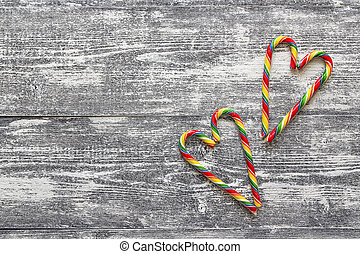 Christmas Candy Canes in the form of heart on gray wooden...
