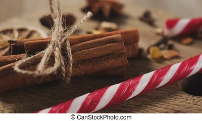 Christmas cane candy and aromatic spices on round board with garland illumination on background