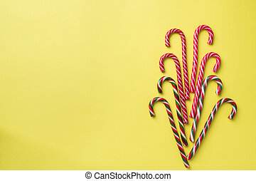 Christmas caramel canes on a yellow background. Holiday festive celebration greeting card with copy space to adding text.