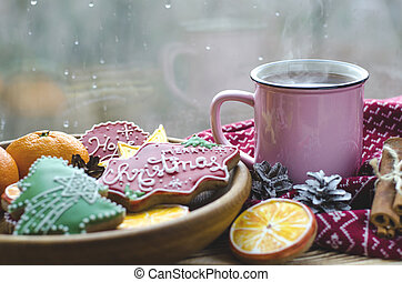 A cup of hot tea stands on a wooden table next to a wooden plate on which are gingerbread cookies made from orange slices against the background of a window with water drops