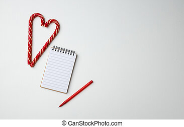 Christmas card and candy canes on white background