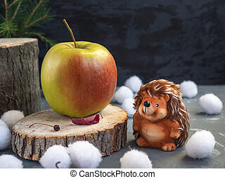 Christmas card. Hedgehog found a large apple on the forest hemp. Snowballs, dry autumn leaves.
