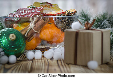 New year's gift stands on a wood table next to the oranges, tangerines, snowflakes and Christmas Toys
