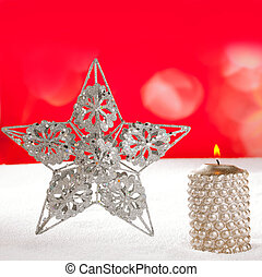 Christmas card of silver star and candle on snow