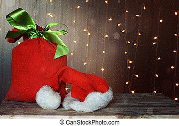 Christmas card with a red bag full of gifts and a Santa Claus hat. Luminous garland in the background.