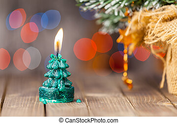 Christmas card with glowing small candle on old wooden background