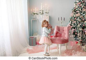 Christmas celebration. Child girl playing near the Christmas tree