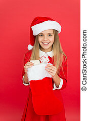 Christmas celebration ideas. Child Santa Claus costume hold stocking. Happy smiling face. Emotional baby. Good vibes. Positivity concept. Cheerful mood. Christmas party. Winter holidays. Playful mood