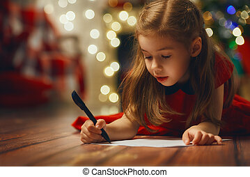 christmas celebration - small child writes the letter to...