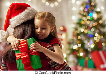 christmas celebration - Mother and daughter exchanging...