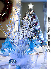 Winter Wonderland theme on this dining room table set for Christmas which includes this centerpiece of lighted branches blue ribbons and bows