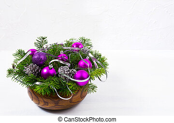 Christmas table centerpiece with fir branch, silver pine cones, glitter and purple baubles in the wooden bowl, copy space.