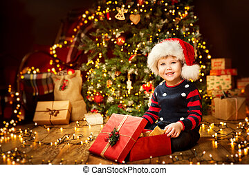 Christmas Child Open Present under Xmas Tree, Happy Baby Boy with New Year Gift Box