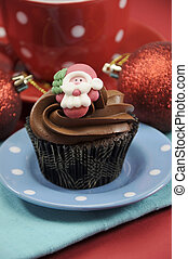 Christmas chocolate cupcakes with Santa faces against a red festive background.