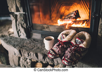 Christmas comfortable slippers by the warm cozy fireplace. ...